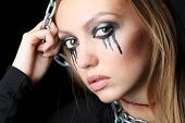 Zombie girl with black tears and cut throat hangs on chain at black background.