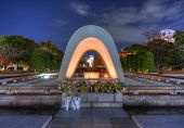 Cenotaph through which the Atomic Dome can be seen at at Peace Memorial Park in Hiroshima, Japan.