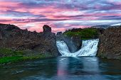 Double waterfall Hjalparfoss on the river Fossa after the midnight sunset with a beautiful vivid dra