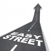 picture of paved road  - Easy Street words on a black paved road with arrow leading upward symbolizing luxurious living - JPG