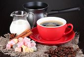 Red cup of coffee with rahat delight, milk and coffee pot on wooden table poster