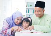Muslim family reading book at home. Southeast Asian family living lifestyle