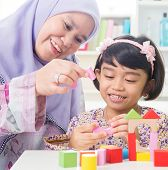 Muslim family building wooden house toy. Southeast Asian family living lifestyle.