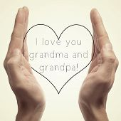 someone holding a drawn heart in his hands and the sentence I love you grandma and grandpa written i