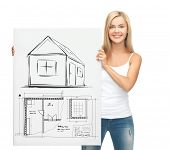 real estate, property, business and accomodation concept - woman holding picture with house and blue