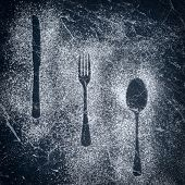 Outlines of knife, fork and spoon made with a dusting of icing sugar