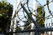 Razor wire and barbwire tangled over a chain link fence