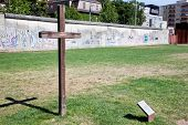 Berlin Wall Memorial with graffiti and cross commemorating the deaths and division. The Gedenkstatte Berliner Mauer