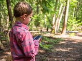stock photo of gps  - Child searching for GPS geocache on trail - JPG