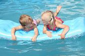 Two children swimming on a inflatable water toy.