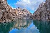 Reflexion of the sky and rocks in Kelsu mountain lake with turquoise colour of water and colourful d