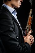 foto of musket  - Photo of young man with musket posing indoors - JPG
