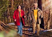 seniors walking in autumn forest / active