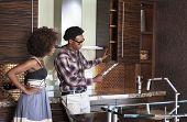 Young African American couple in new furnished Kitchen choosing materials