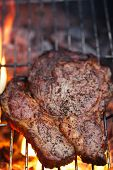 food meat -  rib eye beef steak on party summer barbecue grill with flame. Shallow dof.