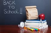 Back to school, school books with apple and  paper bag lunch on desk