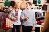 Portrait of amorous couple of shoppers interacting in clothing department