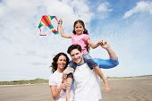 foto of kites  - Family Having Fun Flying Kite On Beach Holiday - JPG