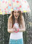 stock photo of raindrops  - Teenage Girl Sheltering From Rain Beneath Umbrella - JPG