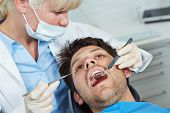 Dentist examining mouth of patient with mirror and probe
