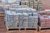 Постер, плакат: Stacks of various colored concrete pavers paving stone or patio blocks organized on wooden pallets