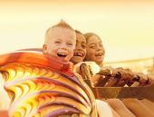 stock photo of carnival ride  - Kids on a Summertime Roller Coaster Ride - JPG