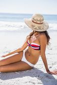Young tanned woman wearing straw hat relaxing on the beach