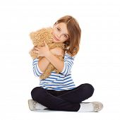 childhood, toys and shopping concept - cute little girl hugging teddy bear
