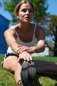 picture of workout-women  - Athletic girl stretching at the track getting ready to run - JPG