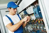 image of electrician  - Young adult electrician builder engineer screwing equipment in fuse box - JPG