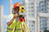 image of geodesic  - builder worker with theodolite transit equipment at construction site outdoors during surveyor work - JPG