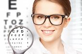 medicine and vision concept - woman with magnifier and eye chart
