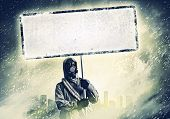 Stalker in gas mask with blank banner. Disaster concept