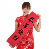 Asian woman with Chinese traditional dress cheongsam or qipao holding couplet, the Chinese word mean