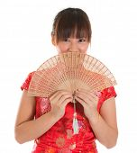 Asian woman with Chinese traditional dress cheongsam or qipao holding Chinese fan covering part of f
