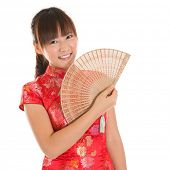 Asian woman with Chinese traditional dress cheongsam or qipao holding Chinese fan. Chinese new year