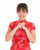 Asian woman with Chinese traditional dress cheongsam or qipao respecting on Chinese New Year Festiva