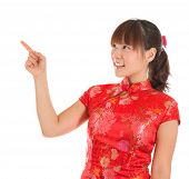 Pretty Asian woman with Chinese traditional dress cheongsam or qipao finger pointing at blank copy s