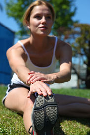 pic of workout-women  - Athletic girl stretching at the track getting ready to run - JPG