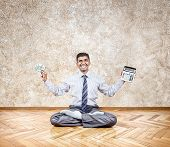 stock photo of indian money  - Happy Indian businessman holding money and calculator in lotus pose - JPG