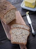 picture of cannabis  - Fresh homemade whole grain wheat bread with linum and cannabis, served with butter
