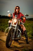stock photo of biker  - Biker girl with sunglasses and motorcycle - JPG