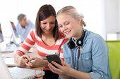 Girlfriends in class using smartphone