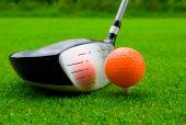 A golf driver with an orange ball