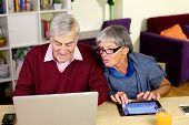 Happy Elder Couple Writing Email To Grandson