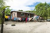 Image of a small stilt home on Kioa Island in Fiji with colorful clothing drying on a laundry clothesline