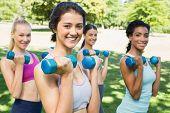 Group portrait of happy multiethnic women lifting dumbbells in park