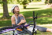 Young female bicyclist with hurt leg sitting on grass in the park