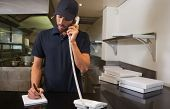 Handsome pizza delivery man taking an order over the phone in a commercial kitchen