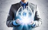 Close up of businessman holding image of lungs in hands